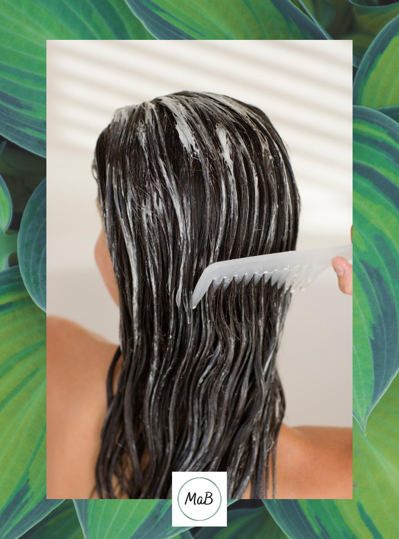 A photograph of a middle-aged woman combing fanola hair mask through her hair. The photograph is taken from the back and is laid over a background of hosta leaves.